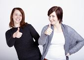 Two Girls Friends Gesturing Thumb Up