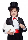 Young magician boy holding white rabbit and magic wand - isolated