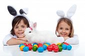 Happy kids at easter time - wearing bunny ears and guarding their white rabbit and colorful eggs