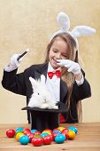 Happy magician girl conjuring up the easter bunny and colorful eggs