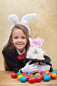Happy magician girl holding cute easter bunny in magic hat - with colorful eggs- shallow depth of field