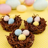 stock photo of nest-egg  - Springtime chocolate nests filled with Easter eggs on a yellow background - JPG
