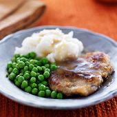 vegan meat alternative fried steak with peas and potatoes