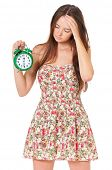 Unhappy beautiful girl with alarm clock, isolated on white background
