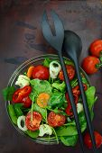 Bowl of fresh colorful salad with fork and spoon on wooden surface