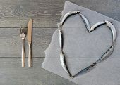 Fresh sardine in heart form and cutlery