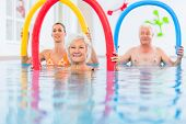 Group  or young and senior people in aquarobic fitness swimming pool exercising with  pool noodle