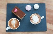 Cup of cappuccino with a beautiful delicious cake on black ceramic stand on a wooden boards backgrou