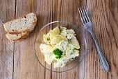 Potato Salad In A Glass Bowl On Wooden Board