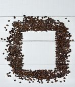 Coffee bean frame on a white wood table. Shot from a high angle with blank space for copy.