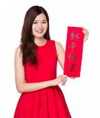 Woman hold with Chinese calligraphy, phrase meaning is happy new year