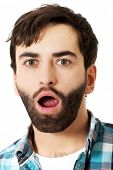 Young handsome shocked man with mouth open.