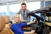 auto business, car sale, consumerism and people concept - happy couple buying car in auto show or salon