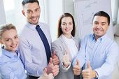 business, teamwork, success, people and gesture concept - smiling business team showing thumbs up in office