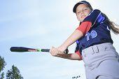 A Baseball girl hitter over a blue sky