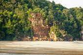 Big cliff rainforest and exotic sand beach