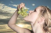 little girl eating bunch of grapes in the outside