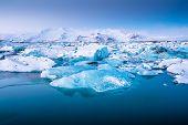 stock photo of iceberg  - Icebergs floating in Jokulsarlon glacier lake at sunset - JPG