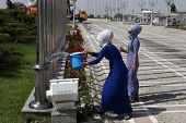 Ashgabat, Turkmenistan - February 26, 2013. Women Engaged In Manual Cleaning Of Streets And Wash Bas