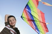 stock photo of kites  - A boy who play with is kite with sky on the background - JPG