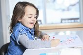 Cheerful little girl colouring at the table at home in kitchen
