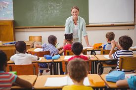 stock photo of classroom  - Pretty teacher talking to the young pupils in classroom at the elementary school - JPG
