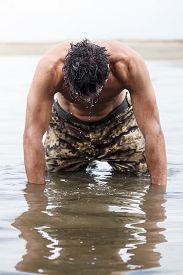 image of wet pants  - Close up Muscled Army in Camouflage Pants Kneeling on the Sea Water After Outdoor Training.