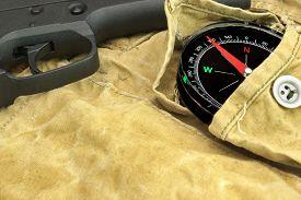 stock photo of handgun  - Modern Handgun and Compass On The Weathered Backpack - JPG