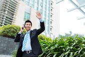 stock photo of waving hands  - Vietnamese businessman waving his hand and talking on the phone - JPG