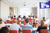 image of speaker  - Speaker giving presentation in lecture hall at university - JPG