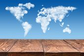 picture of puffy  - empty wooden table with world map made of white puffy clouds on sky as background - JPG