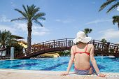 stock photo of sunbather  - Young woman sunbathing at the swimming pool - JPG