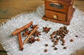 stock photo of cinnamon sticks  - Wooden coffee grinder with coffee beans - JPG