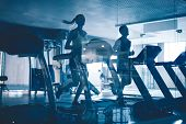 foto of treadmill  - Active young people running on treadmills in sports club - JPG