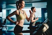 image of treadmill  - Active female running on treadmill in gym with young man on background - JPG