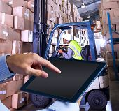 pic of forklift  - Man using tablet pc against forklift machine in warehouse - JPG