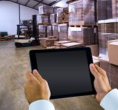 stock photo of forklift  - Man using tablet pc against forklift in a large warehouse - JPG