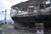 image of reconstruction  - old wooden fishing ship on reconstruction in docks tail - JPG