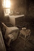 stock photo of abandoned house  - Old vintage appliances lay cluttered on an abandoned farm house room floor  - JPG