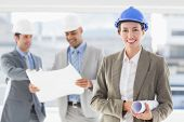 stock photo of hard-on  - Businessmen and a woman with hard hats holding blueprint in the office - JPG
