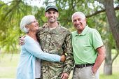 pic of reunited  - Soldier reunited with his parents on a sunny day - JPG