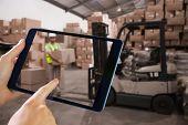 image of pallet  - Man using tablet pc against warehouse worker loading up pallet - JPG