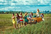 stock photo of towing  - Group of women is pulling a car with the towing cable. Rural road city on the background.