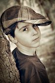 picture of newsboy  - Young boy with newsboy cap leaning on a tree and playing detective - JPG