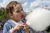 picture of candy cotton  - Boy licks cotton candy in the park - JPG