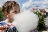 stock photo of candy cotton  - Kid licks cotton candy in the park - JPG