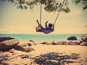 picture of swing  - Young man swinging in a swing on tropical summer beach vintage filter effect - JPG