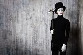 stock photo of mime  - Elegant expressive male mime artist posing with walking stick by a grunge wall - JPG