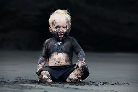 picture of wet feet  - Funny portrait of smiling child with dirty face sitting and playing with fun on black sand sea beach before swimming in ocean - JPG