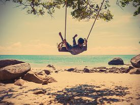 stock photo of swing  - Young man swinging in a swing on tropical summer beach vintage filter effect - JPG